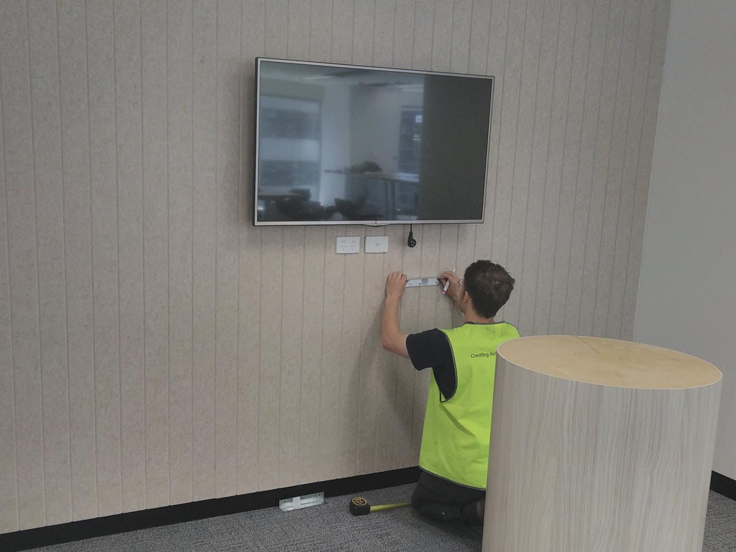 AV Technician installing TV on wall.